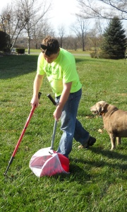 Jason Smith scooping dog waste while customer Crystal the Lab supervises