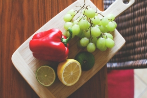 Fresh grapes, pepper, lemon, and lime on a cutting board. BY VIKTOR HANACEK